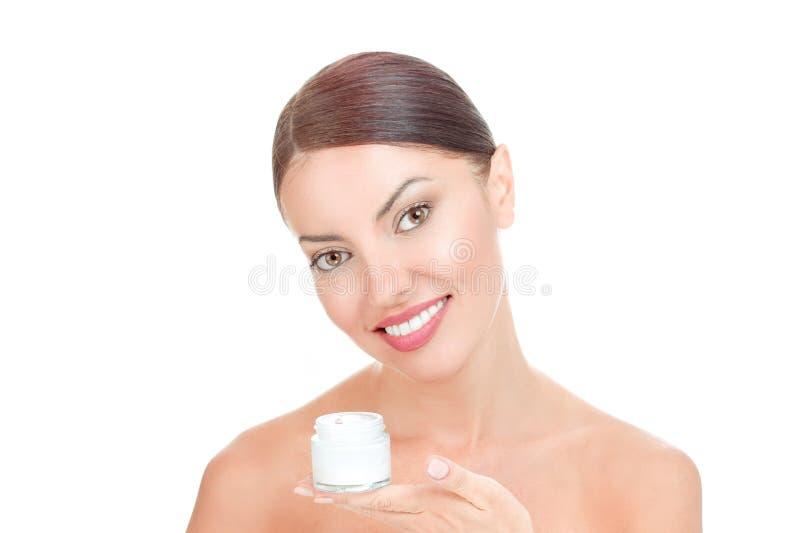 Kobieta patrzeje kamery uśmiechniętego toothy mienia kremową butelkę fotografia royalty free