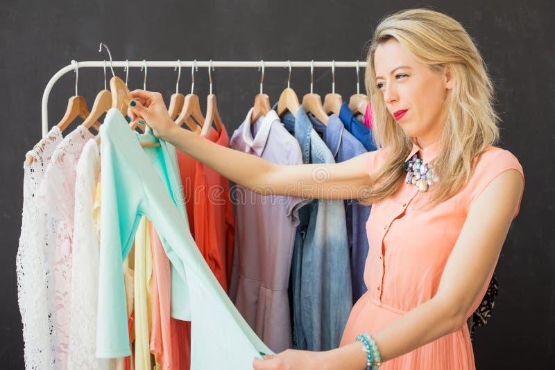 Kobieta patrzeje kawałek odzież fotografia stock