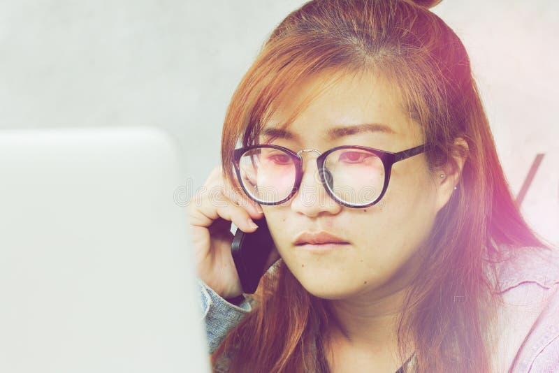 Kobieta patrzeje komputer w szkłach i czekać na telefon komórkowego obrazy royalty free