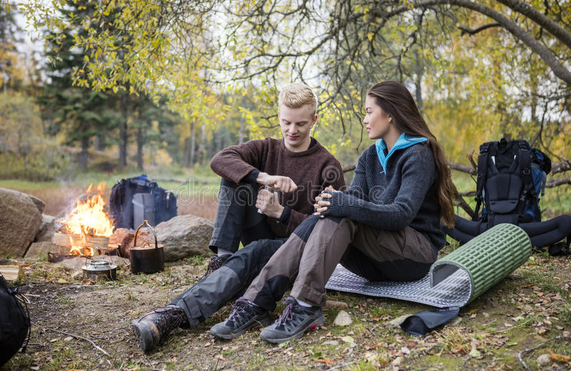Kobieta Patrzeje mężczyzna Szlifierską kawę Podczas campingu W lesie fotografia stock