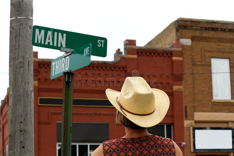 Kobieta patrzeje Main Street podpisuje wewnątrz Ameryka fotografia stock