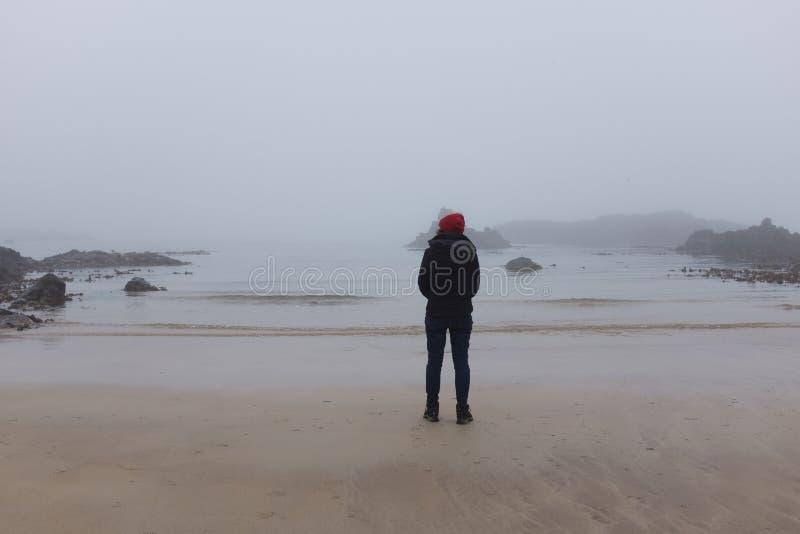 Kobieta patrzeje ocean z powrotem kamera, zimny dzie? zdjęcia royalty free