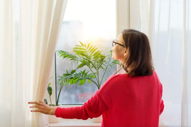 Kobieta patrzeje out okno, otwiera zasłony widok z powrotem fotografia stock
