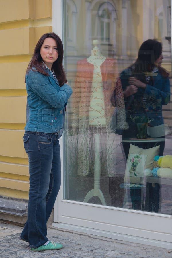 Kobieta patrzeje pokazywać okno lub robić zakupy fotografia royalty free