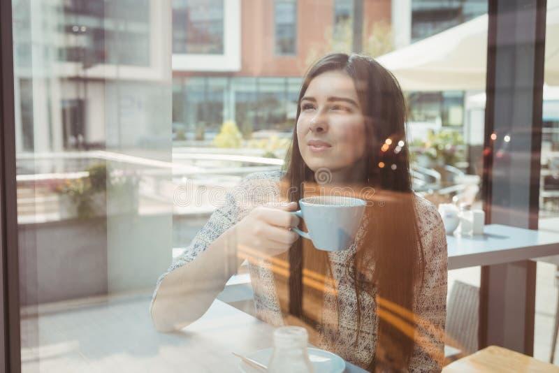 Kobieta patrzeje przez okno z kawą zdjęcia royalty free