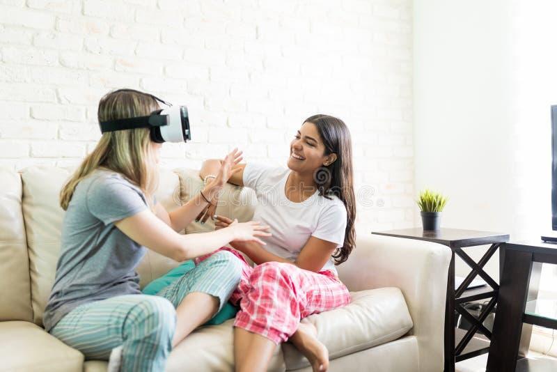 Kobieta Patrzeje przyjaciela Jest ubranym rzeczywistości wirtualnej słuchawki W Domu obrazy royalty free