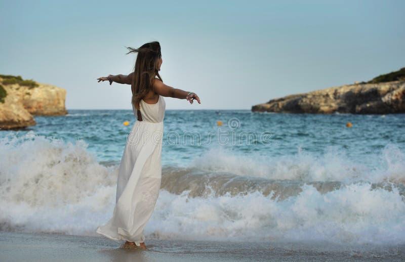 Kobieta patrzeje rozważny przy wodą morską w wakacje letni cieszy się wakacje relaksującego będący ubranym biel plaży suknię zdjęcia stock
