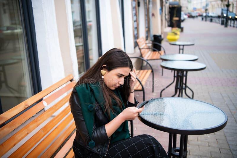 Kobieta patrzeje smartphone przy ulicznym cukiernianym uczucia spęczeniem obraz royalty free