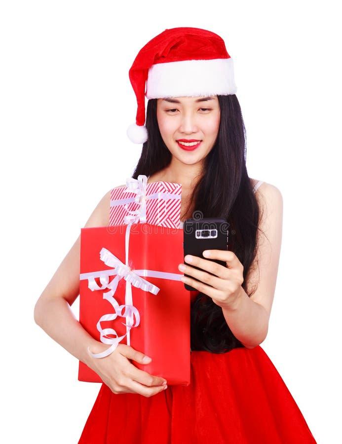Kobieta patrzeje telefon komórkowego z prezenta b w Święty Mikołaj ubraniach zdjęcie royalty free