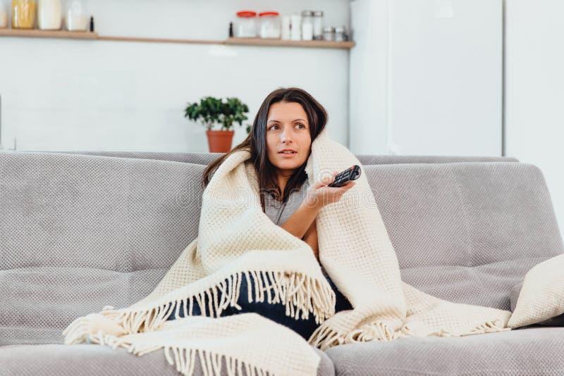 Kobieta patrzeje TV na leżance Piękna kobieta ogląda TV spadał uśpiony fotografia stock