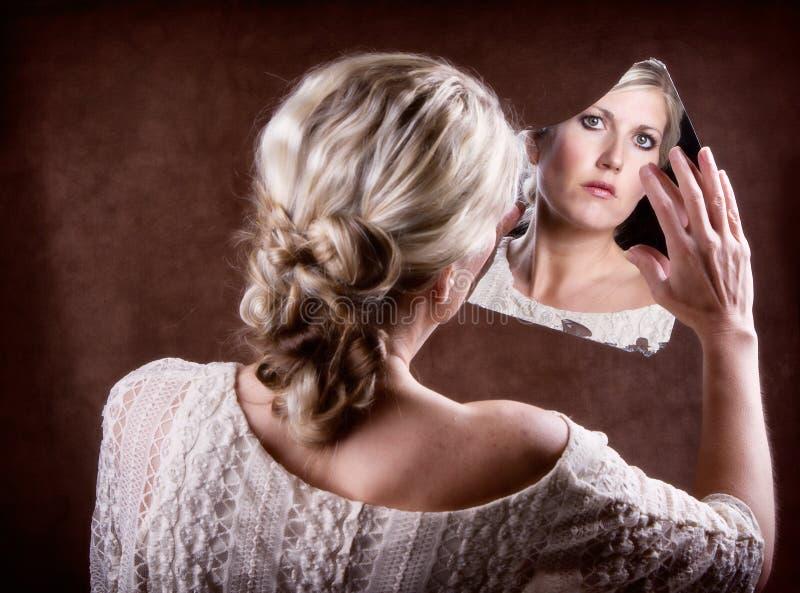 Kobieta patrzeje w łamanego lustro zdjęcie royalty free