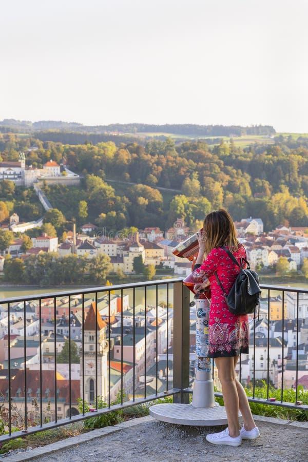 Kobieta patrzeje w lornetkach cieszy się pejzażu miejskiego widok przez miasta zdjęcie stock