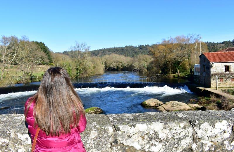 Kobieta patrzeje widok z długie włosy na moście Rzeka, siklawa i las z niebieskim niebem, Ponte Maceira, Hiszpania fotografia stock
