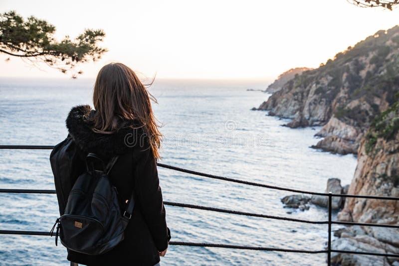 Kobieta patrzeje zmierzch na skalistej falezy linii brzegowej obraz stock
