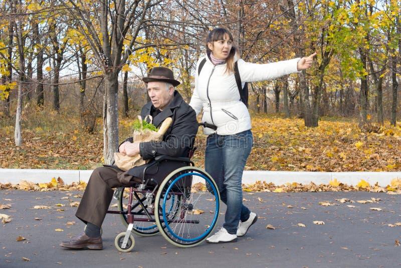 Kobieta pcha starszego mężczyzna w wózku inwalidzkim obraz stock