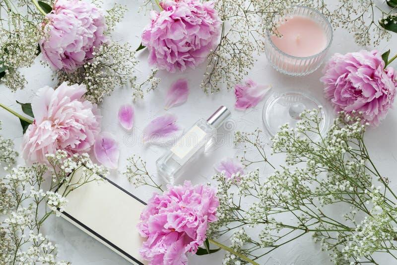 Kobieta, piękna blogger mieszkanie nieatutowy - pachnidło butelka, peonie, łyszczec kwitnie na marmurowym tle fotografia stock