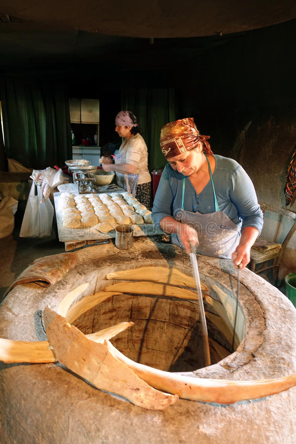 Kobieta piec tradycyjnego Gruzińskiego chleb fotografia royalty free