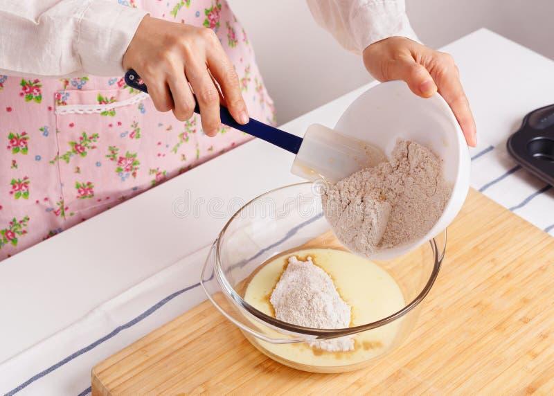 Kobieta piec zdrowy słodka bułeczka z mąką mieszał zmielonego flaxseed obrazy royalty free