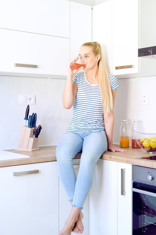 Kobieta pije domowej roboty owocowego soku obsiadanie na kuchennym kontuarze Młoda gospodyni domowa relaksuje w kuchni obraz royalty free