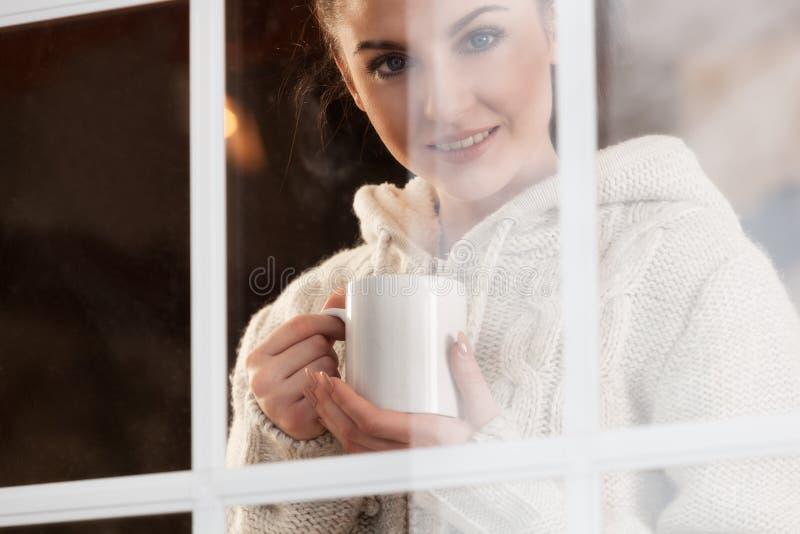 Kobieta pije gorącą napój pozycję okno fotografia royalty free