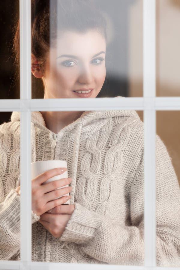 Kobieta pije gorącą napój pozycję okno zdjęcie stock