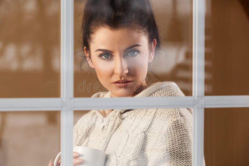 Kobieta pije gorącą napój pozycję okno obrazy stock