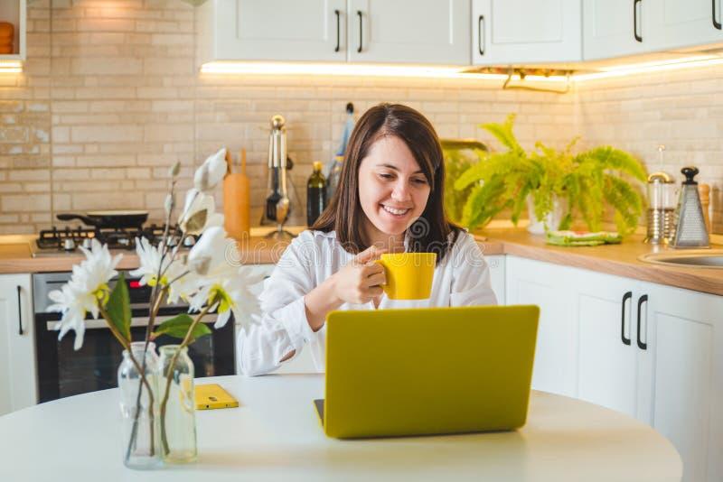 Kobieta pije herbaty od żółtego kubka pracuje na laptopie Kuchnia na tle fotografia stock