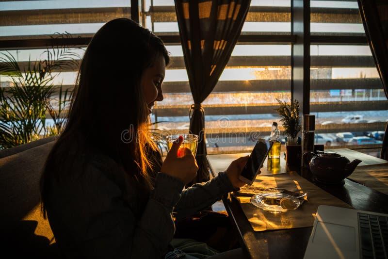 Kobieta pije herbaty w kawiarni i działaniu obraz stock