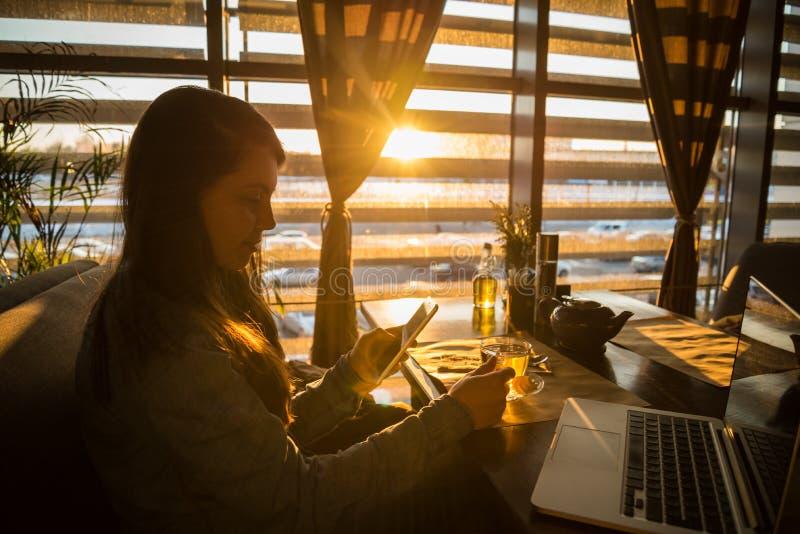 Kobieta pije herbaty w kawiarni i działaniu zdjęcia stock