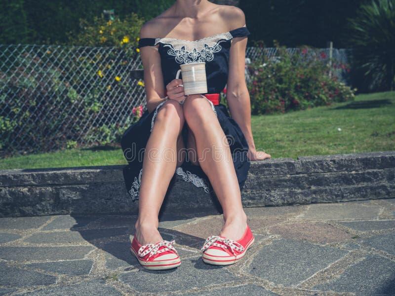 Kobieta pije herbaty w ogródzie zdjęcie stock