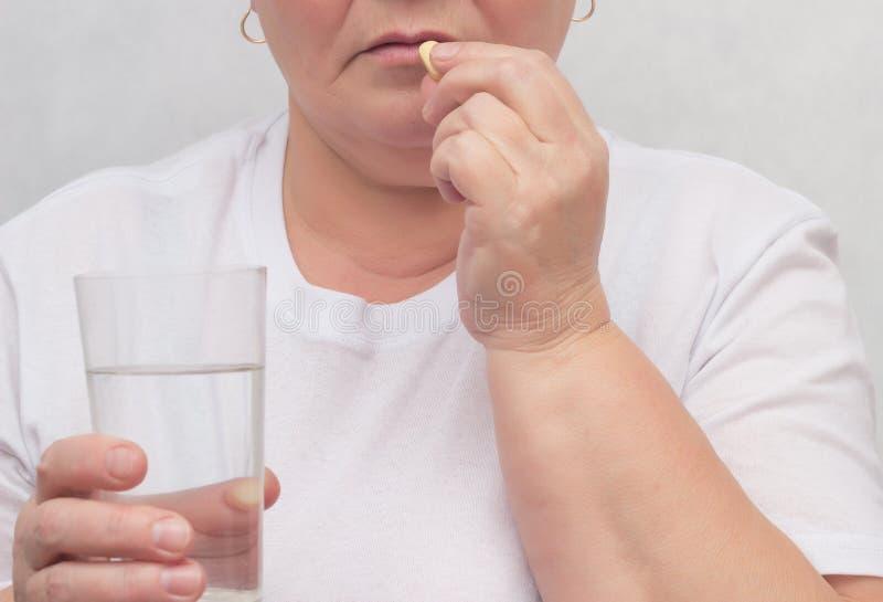 Kobieta pije hormonalną pigułkę dla taktować tarczycowego gruczoł, eliminujący buły i normalizacyjnych hormony, traktowanie, w gó zdjęcia royalty free