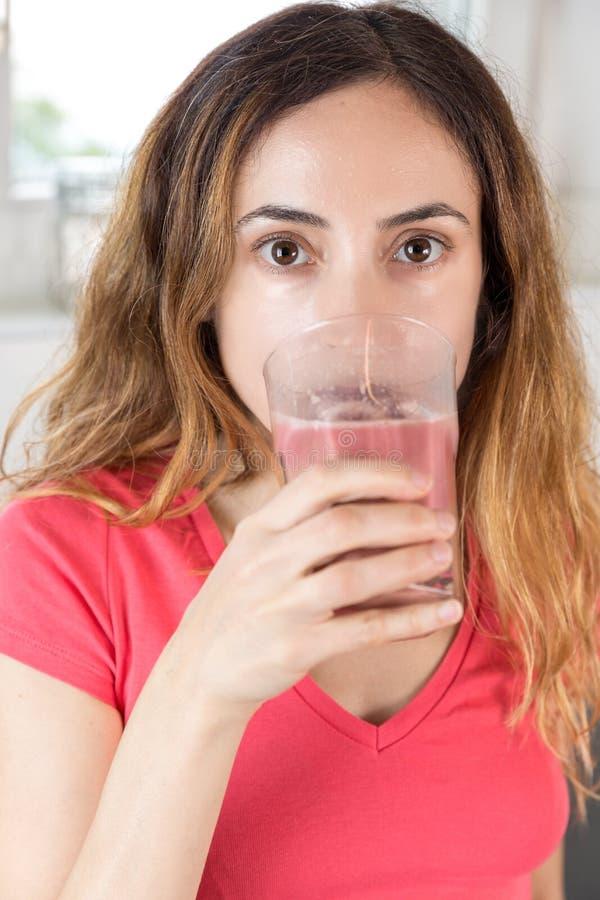 Kobieta pije jagodowego smoothie zdjęcie stock