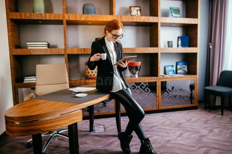Kobieta pije kawę i czytanie jej pastylka podczas gdy stojący w biurze fotografia royalty free