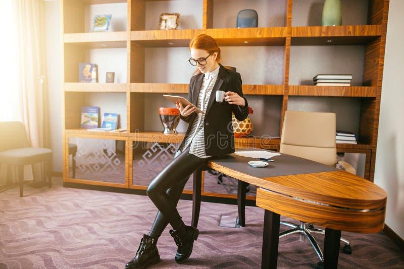 Kobieta pije kawę i czytanie jej pastylka podczas gdy stojący w biurze obrazy royalty free