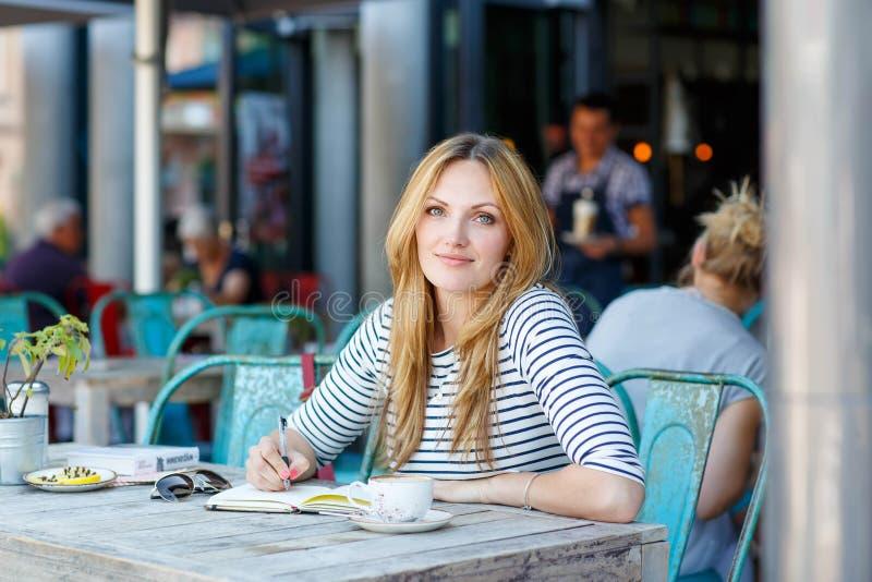 Kobieta pije kawę i pisze notatkach w kawiarni obrazy stock