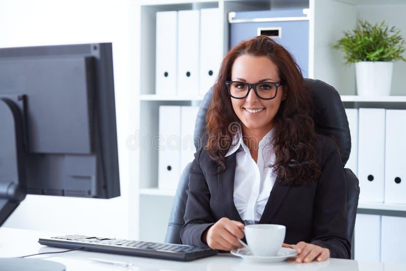 Kobieta pije kawę w biurze zdjęcia stock