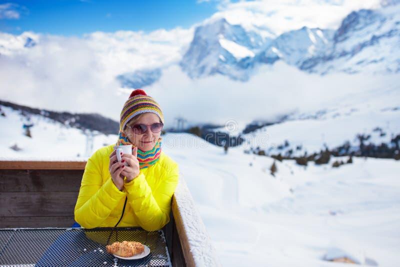 Kobieta pije kawę w górach po narty zdjęcia stock