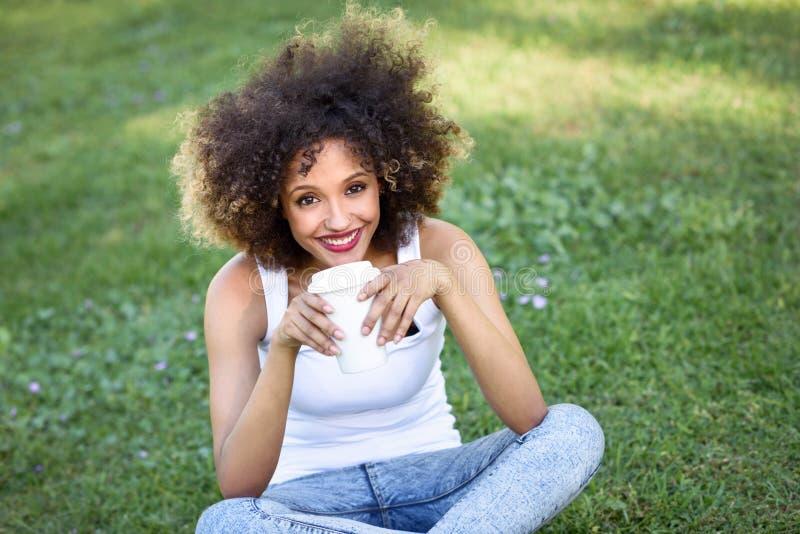 Kobieta pije kawę w parku z afro fryzurą fotografia stock