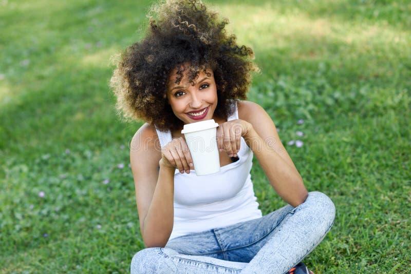 Kobieta pije kawę w parku z afro fryzurą fotografia royalty free
