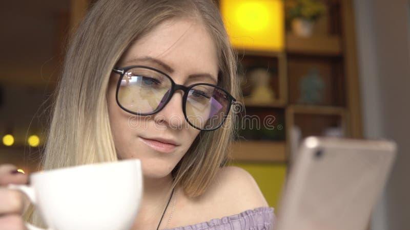 Kobieta pije kawę z telefonem komórkowym zdjęcie stock