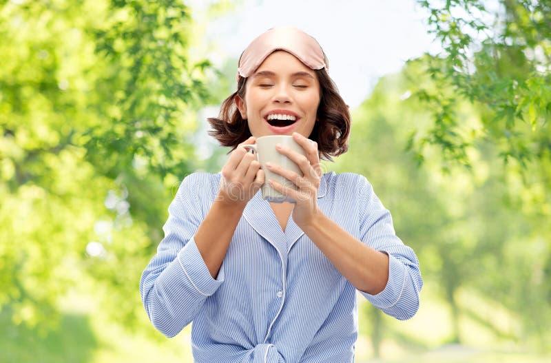 Kobieta pije kaw? w pi?amy i dosypiania masce obraz stock