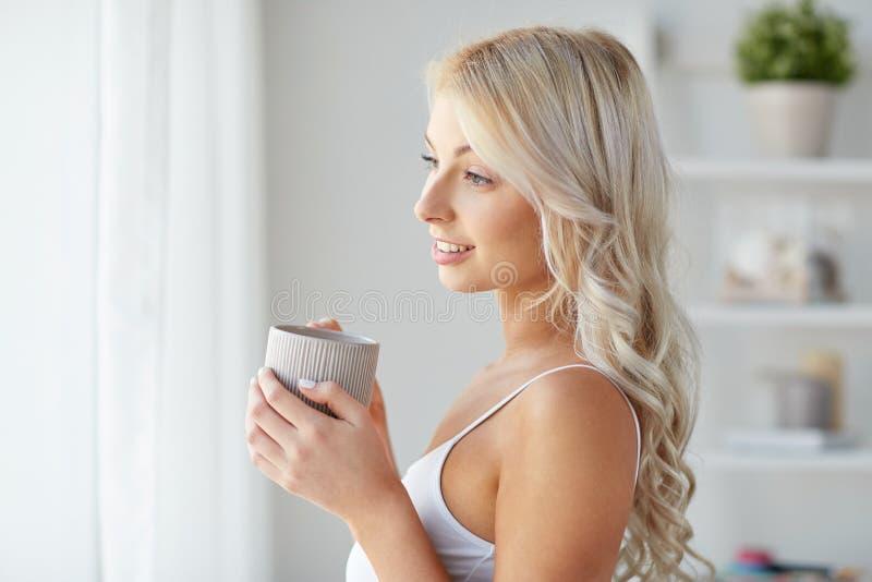 Kobieta pije kawy okno w domu w bieliźnie zdjęcie royalty free