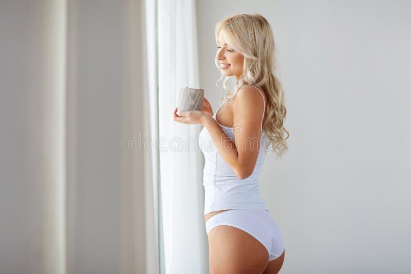 Kobieta pije kawy okno w domu w bieliźnie zdjęcia royalty free