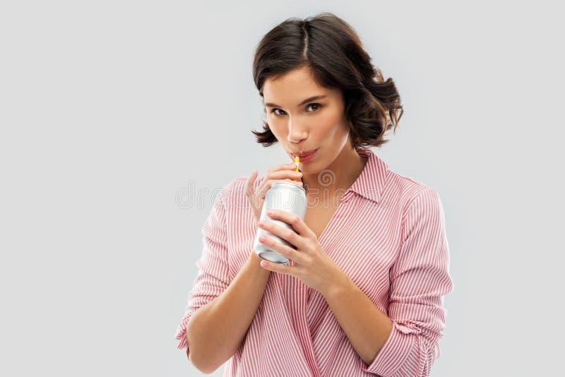 Kobieta pije sod? od puszki z papierow? s?om? zdjęcie royalty free