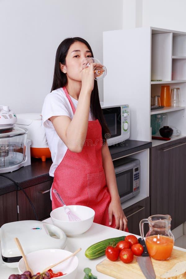 Kobieta pije sok pomarańczowego w kuchennym pokoju zdjęcia stock