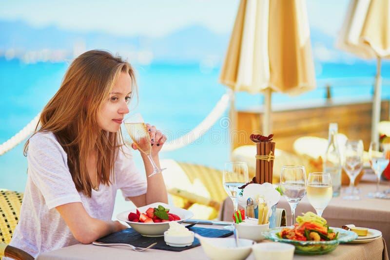 Kobieta pije szampana i je owoc w plażowej restauraci podczas jej urlopowych półdupków morze obrazy stock