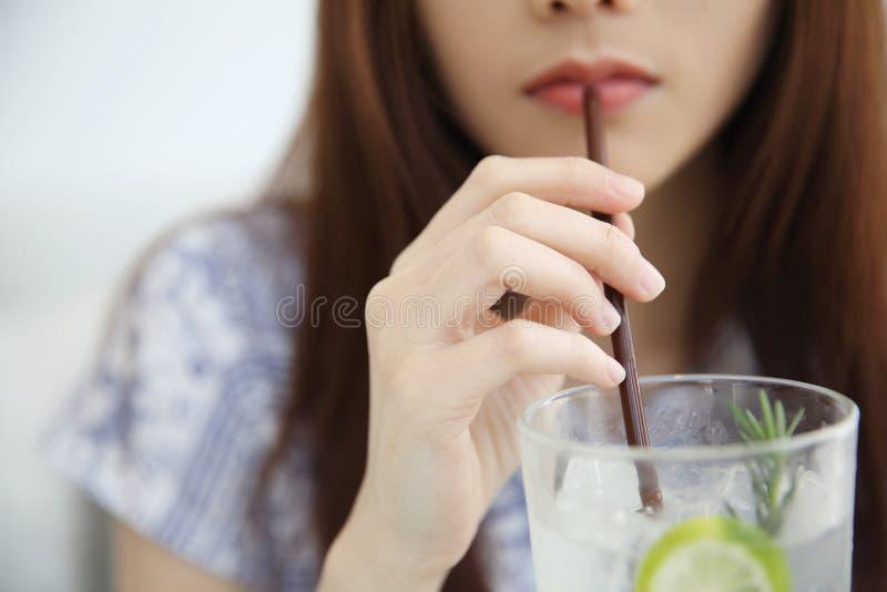 Kobieta pije wapno sok w białym coffeeshop obraz royalty free