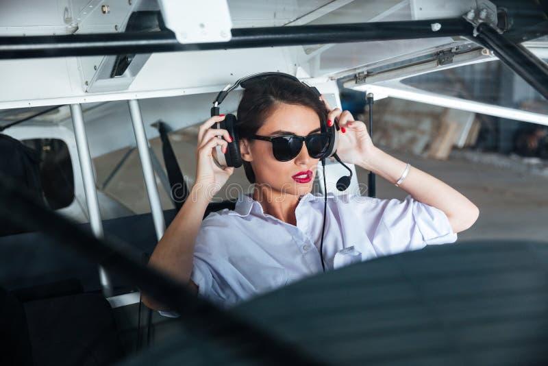Kobieta pilot w słuchawki przygotowywającej latać w małym samolocie zdjęcia royalty free