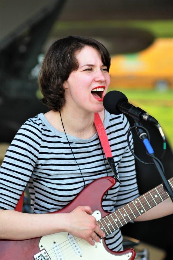 Kobieta piosenkarz bawić się gitarę elektryczną zdjęcie stock