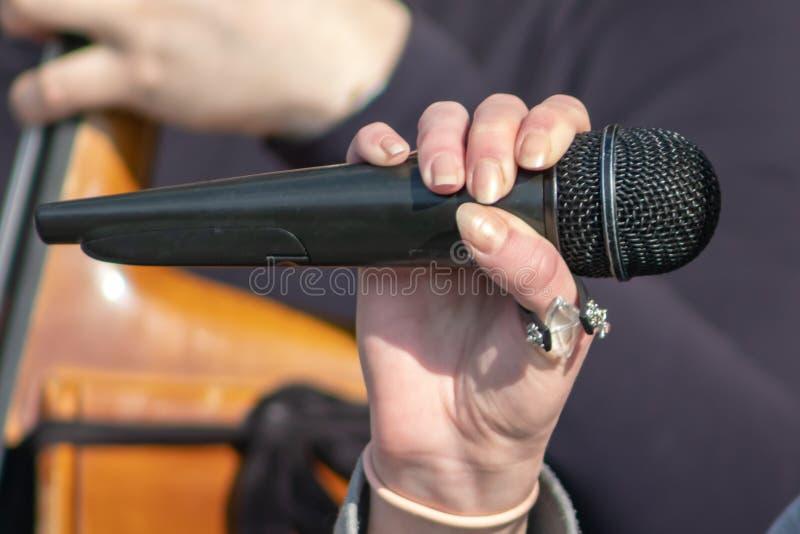 Kobieta, kobieta piosenkarza ręka z mikrofonem zamkniętym w górę puzonu amd muzyk ręka na tle zdjęcia stock